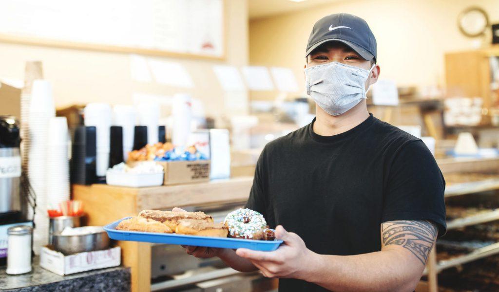 Man holding donuts at Chuck's Donuts in Renton, Washington.