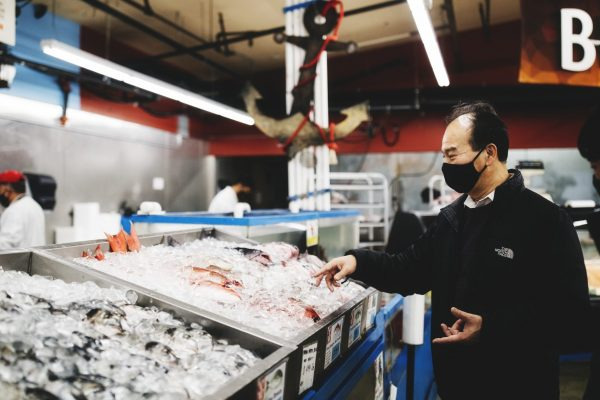 Man stands over fish at local supermarket in Renton, Washington.